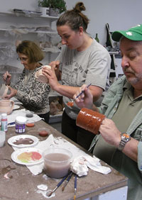 Glazing pottery in an adult clay class.