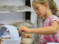 Glazing a pottery basket during clay class for children, tweens and teens